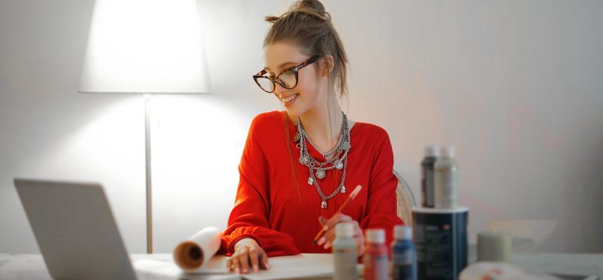 Como se vestir bem para o trabalho: mulher loira de óculos, blusa vermelha de mangas compridas e cabelo preso em coque sentada no seu Home Office, sorrindo olhando para o computador.