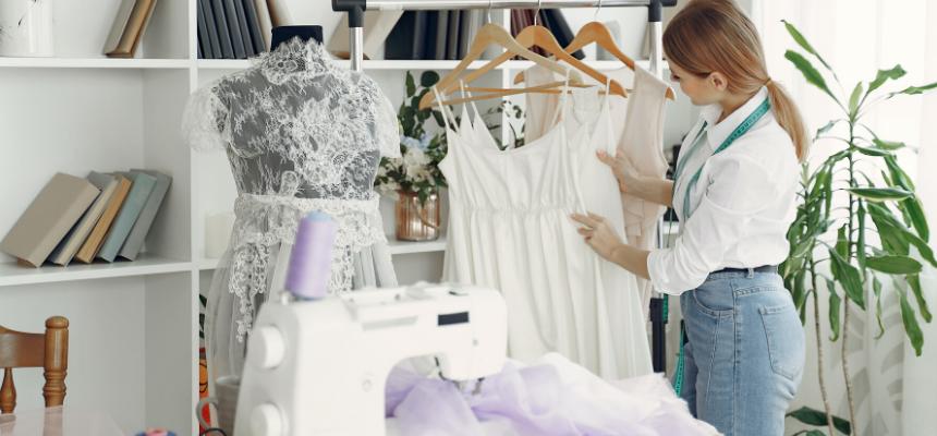 Semanas de moda: estilista loira vista de lado, com as mãos em vestido branco pendurado em cabide no seu ateliê.