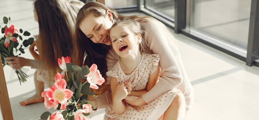 Tipos de mães na moda: mãe agachada usando roupa de cor nude, sorrindo e segurando a filha de 6 anos de idade no colo. Na mão direita, ela segura um ramalhete de flores. Mãe e filha estão sorrindo.
