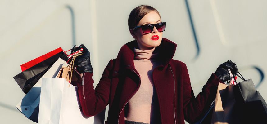 Importância dos acessórios no look. Mulher segurando várias sacolas de compras, vestindo blusa rosa de gola alta e casaco vinho. Ela usa óculos marrom, cabelo preso e batom vermelho.