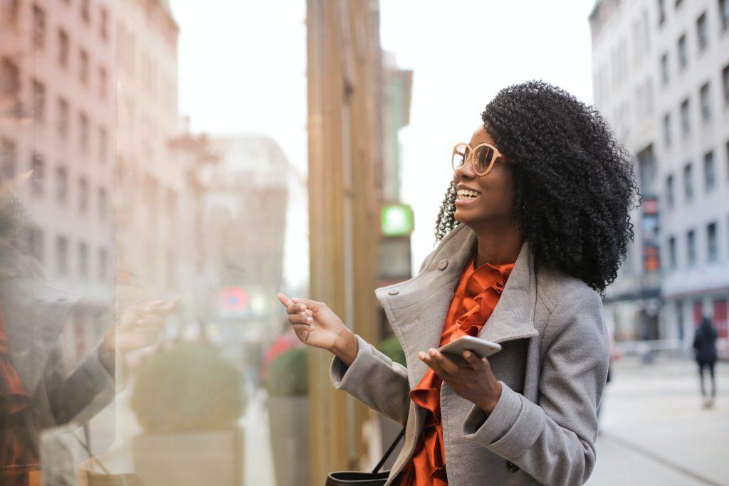 Tipos de corpo feminino: mulher negra sorridente e elegante andando na rua